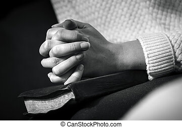 Woman prays with folded hands on the bible