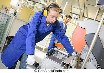 Woman preparaing to cut metal with circular saw