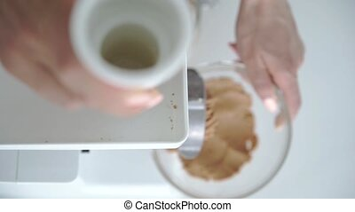 woman prepare peanut butter mincing machine.