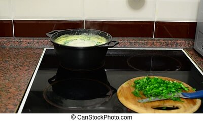 Woman prepares cheese soup in kitchen