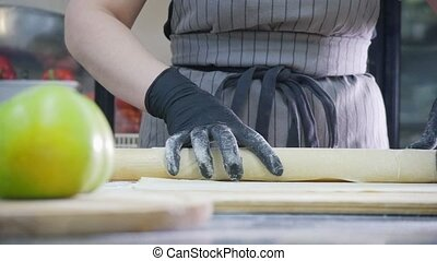 Woman prepares dough for apple pie in commercial kitchen
