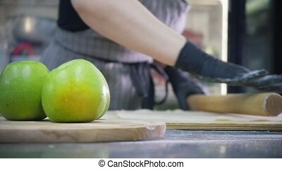Woman prepares dough for apple pie in commercial kitchen, ...
