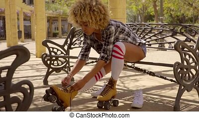 Woman Prepares For Roller Skating Outdoors - Young exotic...