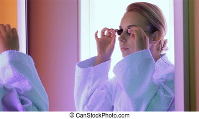 Woman prepares for the tanning at the tanning booth - Pretty...