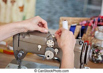 Woman prepares sewing machine