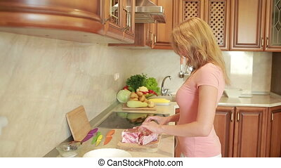 woman prepares the meat in the kitchen. home cooking dinner. Beef steaks