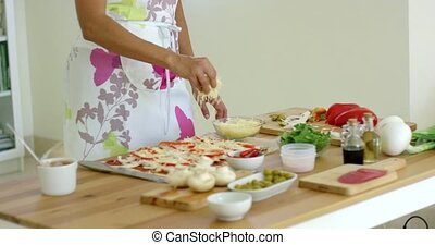 Woman preparing a homemade pizza in the kitchen