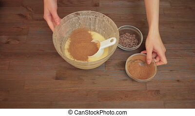 Woman preparing a muffins on the kitchen mixes ingredients