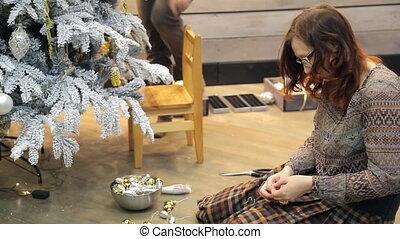 Woman preparing Christmas decorations sitting on floor inside studio