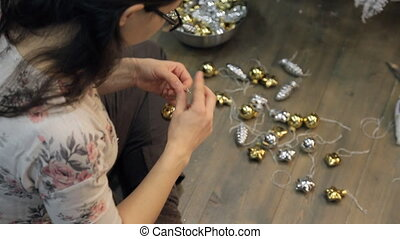 Woman preparing Christmas decorations ties ribbons to decorate studio