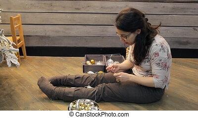 Woman preparing Christmas decorations to decorate studio