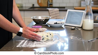 Woman preparing cookies in kitchen at home 4k - Mid section...