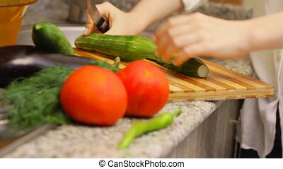 Woman preparing cucumbers