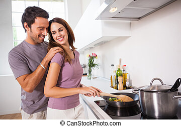 Woman preparing food at the stove with partner behind her in...