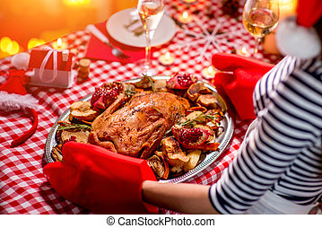 Woman preparing for Christmas dinner - Woman putting on the...