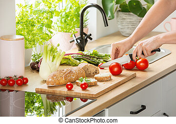 Woman preparing healthy breakfast, cutting a tomato in half and organic herbs and vegetables in a sunny kitchen interior