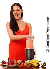 Woman preparing healthy fresh fruit smoothie.