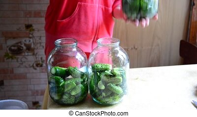 woman preparing homemade canned cucumbers for winter