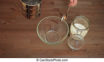 Woman preparing on the kitchen, sifting flour.