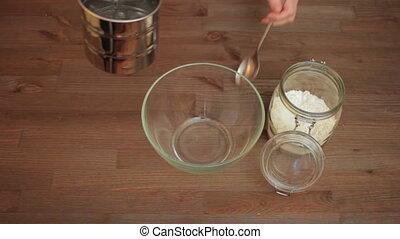 Woman preparing on the kitchen, sifting flour.