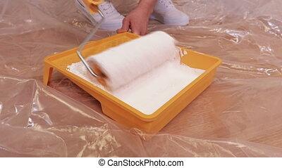 Woman preparing paint roller brush