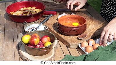 Woman preparing plum tart outdoors