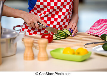 Woman preparing salad in the kitchen