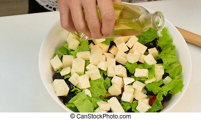 Woman preparing salad vegetables and watering it with olive oil.