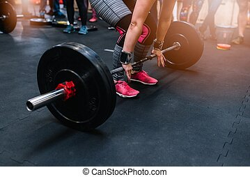 Woman preparing to barbell deadlift