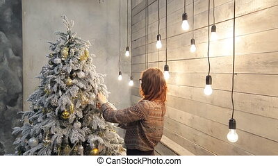 Woman preparing to holidays to decorate Christmas toys indoors