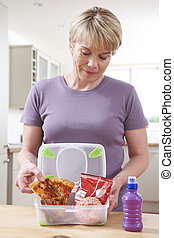 Woman Preparing Unhealthy Lunchbox In Kitchen