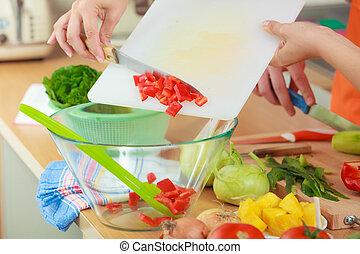Woman preparing vegetables salad slicing red pepper