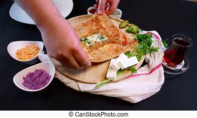 Caucasian woman putting crepe on a wooden board on a black background. Prep scene before shooting.