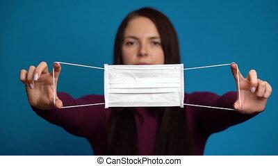 woman presenting a hand flu mask.