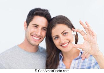 Woman presenting a silver key