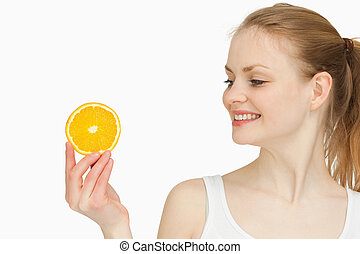 Woman presenting an orange slice while looking at it against...