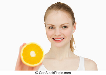 Woman presenting an orange while smiling