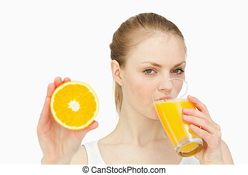 Woman presenting an orange while drinking