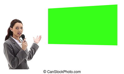 Businesswoman with microphone presenting chroma key