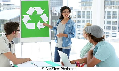 Woman presenting environmental awareness plan to colleagues...