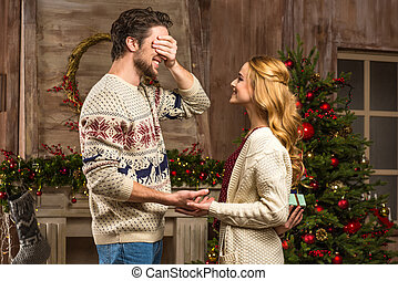 Woman presenting gift box to man