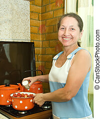 Woman preserving strawberry preserves  in the kitchen