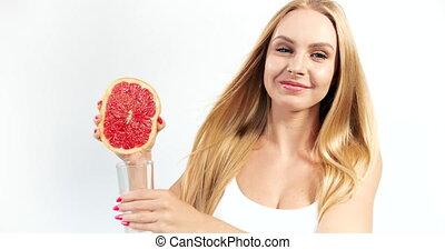 Woman Pressing Grapefruit Juice to Glass - Joyful blonde...