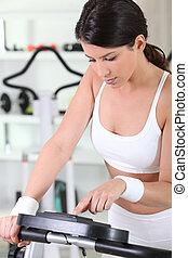 Woman programming an exercise machine