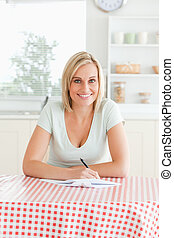 Woman proof-reading a text in the kitchen