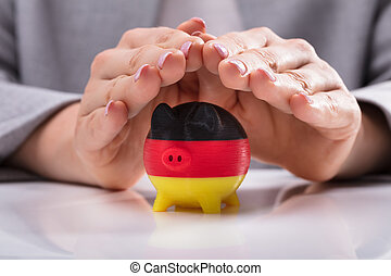 Woman Protecting Piggybank Painted With German Flag