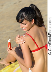 Woman protecting skin with suntan lotion in her shoulder