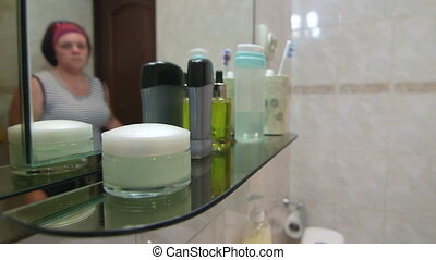 Woman protects skin doing household chores applying moisturizer hand lotion