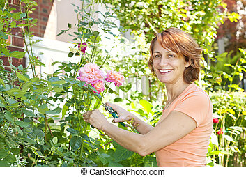 Woman pruning rose bush - Happy woman gardening and pruning...