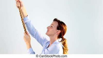 Woman pulling a rope against white background 4k - Smiling...